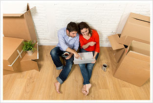 Couple sitting on floor in their new house purchased recently on mortgage