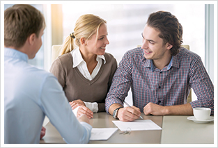 young smiling couple signing with a mortgage broker