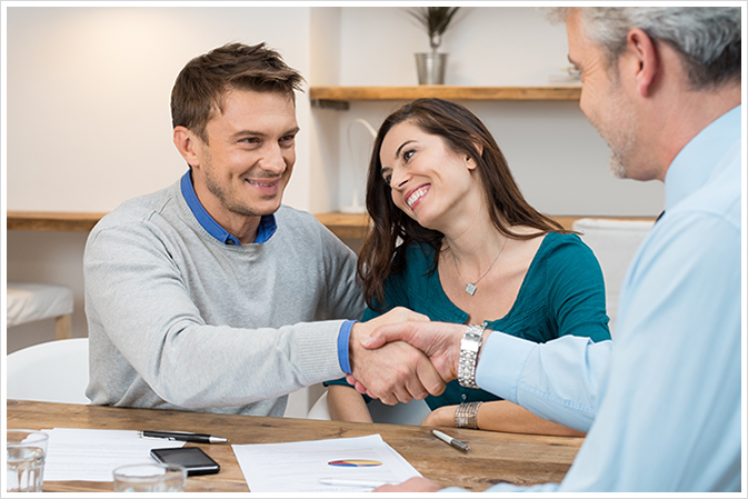 A happy couple completing their mortgage refinancing with a broker